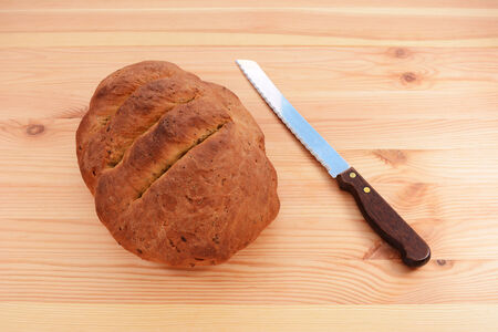 bread knife: Freshly baked seeded loaf with a bread knife on a wooden table