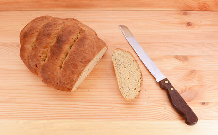 bread knife: Bread knife with a freshly baked seeded loaf, first crust sliced off Stock Photo