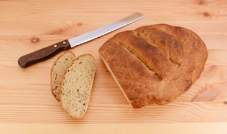 bread knife: Slices cut from a multi seed malted loaf with a sharp bread knife on a table
