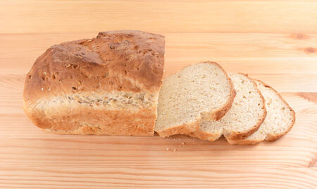 pine three: Crusty loaf of fresh bread with three cut slices on a pine table Stock Photo