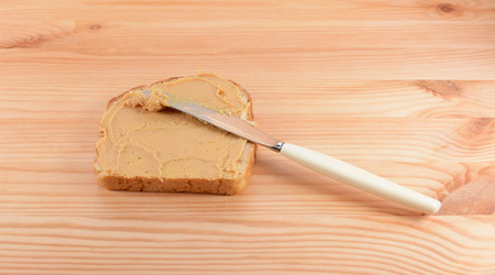 Slice of fresh bread being spread with smooth peanut butter, on a wooden table