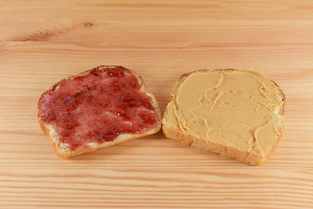 pb: Slices of fresh oat and linseed bread with jelly and peanut butter on a wooden kitchen table