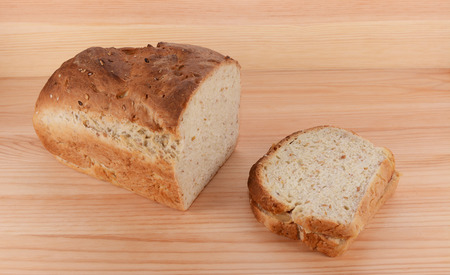 pb: Cut loaf of freshly baked bread with a peanut butter and jelly sandwich on a wooden table Stock Photo
