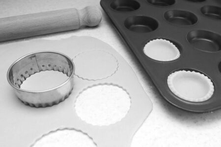 pastry cutter: Lining a bun tin with circles of rolled out pastry to make mince pies, with a rolling pin on the worktop - monochrome processing
