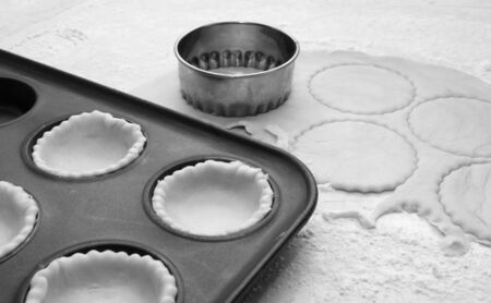 metal monochrome: Pastry circles being cut and lining a metal bun tin for jam tarts - monochrome processing Stock Photo