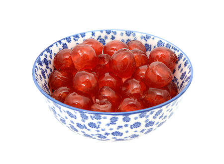 glace: Sticky red glace cherries in a blue and white porcelain bowl with a floral design, isolated on a white background Stock Photo