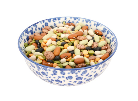 Mixed dried beans - black turtle beans, flageolet beans, pinto beans, brown beans, haricot beans and split peas -  in a blue and white porcelain bowl with a floral design, isolated on a white background photo