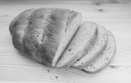 malted: Freshly cut slices of seeded bread fanned out from a new loaf - monochrome processing Stock Photo