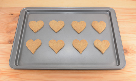 cookie sheet: Eight plain heart-shaped biscuits on a cookie sheet, fresh from the oven