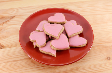 Red plate stacked high with frosted heart-shaped cookies for Valentines Day, on a wooden table photo