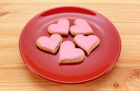 Five heart-shaped iced biscuits on a red plate for Valentines Day, on a wooden table photo