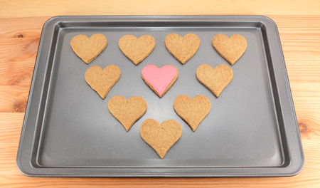 cookie sheet: Plain heart-shaped biscuits on a cookie sheet, with one pink iced cookie in the centre Stock Photo