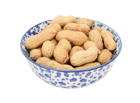 monkey nuts: Monkey nuts in a blue and white porcelain bowl with a floral design, isolated on a white background Stock Photo