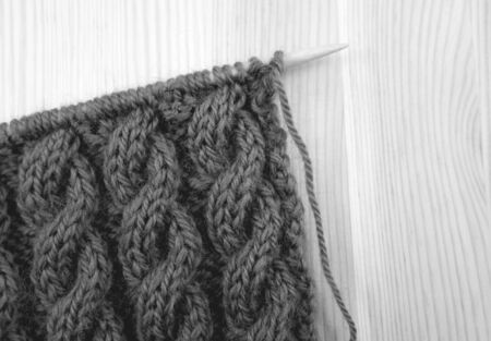 cable stitch: Coiled rope cable knitting stitch on the needle, on a wooden background - monochrome processing