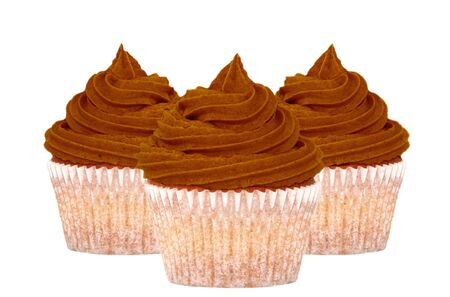 piped: Three chocolate cupcakes with swirls of icing, isolated on a white background