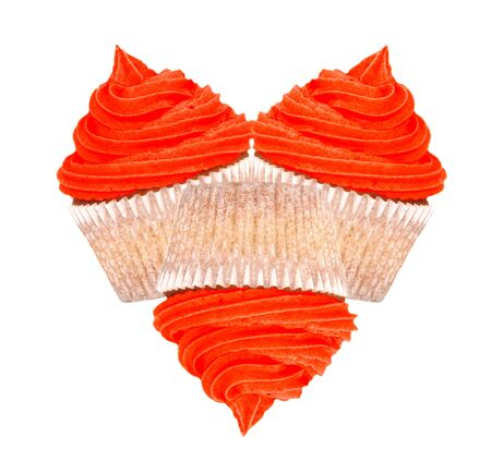 Heart-shaped arrangement of three cupcakes with red frosting for Valentines Day, isolated on a white background Stock Photo