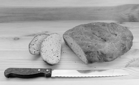 bread knife: Bread knife with slices of bread cut from a seeded loaf of bread - monochrome processing