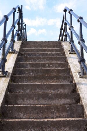 concrete steps: Flight of weathered concrete steps leads upwards into the blue sky