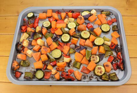 butternut squash: Roasted vegetables on a baking tray - courgette, sweet potato, butternut squash, red and green peppers, parsnip and red onion