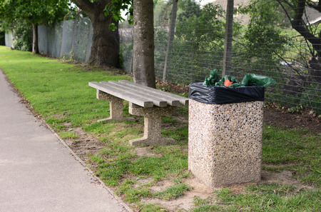 rubbish bin: A full rubbish bin makes an empty bench an unwelcoming place to rest