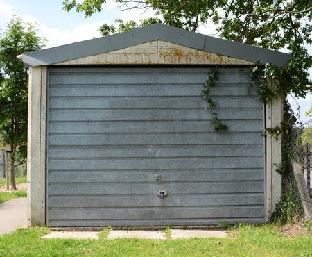 Free-standing garage with a locked, unpainted metal door, overgrown with ivy photo