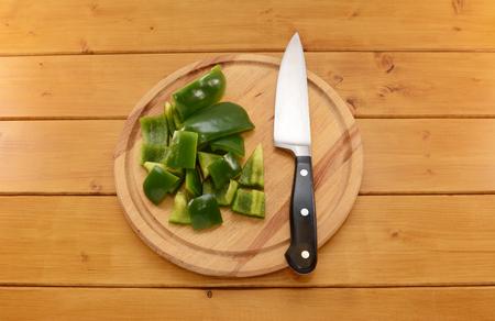 cuchillo de cocina: Pimiento verde crudo se corta en trozos con un cuchillo de cocina afilado en una tabla de cortar de madera