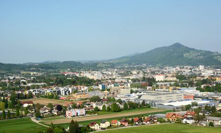 outskirts: Aerial view of the outskirts of the city of Salzburg, Austria, with colourful houses, industrial buildings and construction sites among the hills