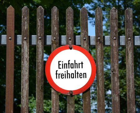 instructs: Round German sign on a wooden fence instructs Keep entrance clear - Einfahrt freihalten