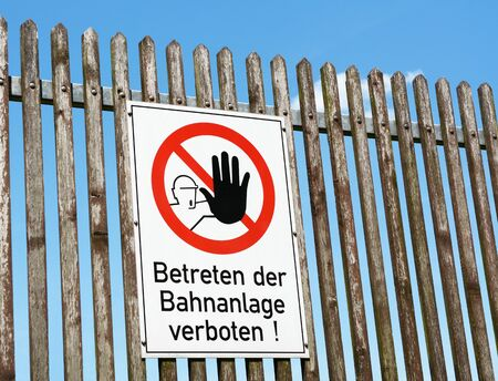 instructs: German safety sign instructs the public to keep off the railway beyond the fence - Betreten der Bahnanlage verboten!