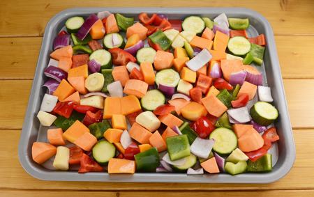 butternut squash: Chopped raw vegetables seasoned and drizzled with oil in preparation for roasting-  red pepper, parsnip, sweet potato, courgette, red onion, butternut squash, green pepper
