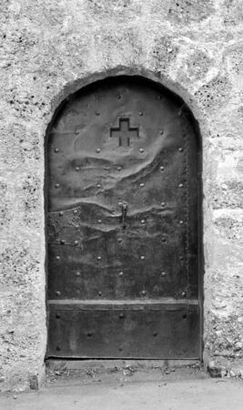 metal monochrome: Old studded metal door, decorated with a cross and engraving, in a stone wall in Salzburg, Austria - monochrome processing