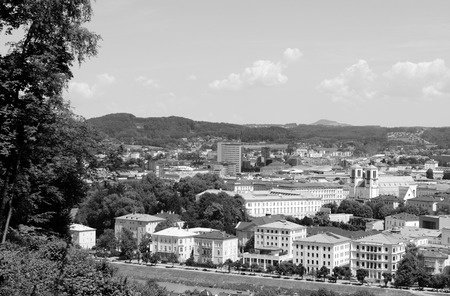 salzach: View over Salzburg city in Europe, from Elisabethkai beside the Salzach river, across Mirabell Palace and St. Andrews Church to the main railway station beyond - monochrome processing Stock Photo
