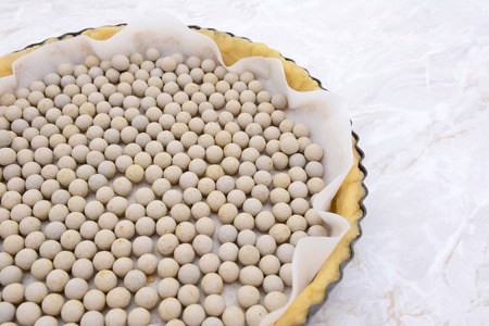 Close-up of pastry weights, ceramic beans, in an unbaked pie case lined with baking parchment