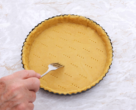 Woman finishes pricking holes in a shortcrust pastry pie crust for blind baking