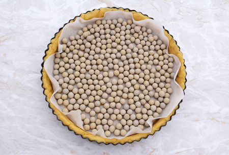 Ceramic beans used as pastry weights in an uncooked pie crust lined with greaseproof paper