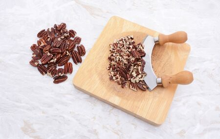 whole pecans: Whole toasted pecans with a rocking knife chopping the nuts on a board