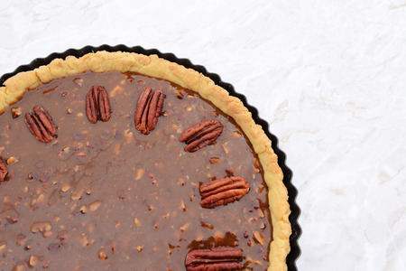 pecan pie: Close-up of whole pecan nuts decorating the top of an unbaked pecan pie Foto de archivo