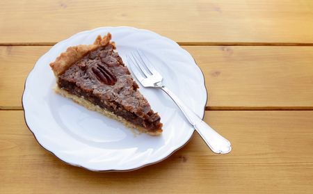 pecan pie: Slice of freshly-baked pecan pie on a china plate with a dessert fork
