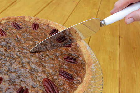pecan pie: Woman cutting into a home-made pecan pie on a wooden table