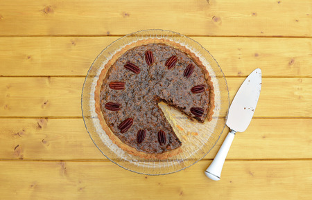 pecan pie: First slice removed from pecan pie on a glass plate, with a dirty pie server beside