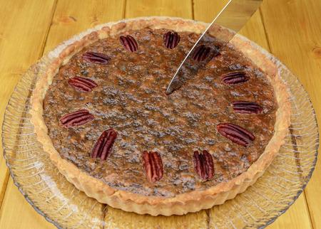 pecan pie: Empezar a cortar un pastel de nuez reci�n horneado en una mesa de madera