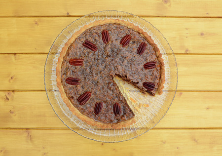 pecan pie: Traditional pecan pie topped with toasted nuts with a slice missing