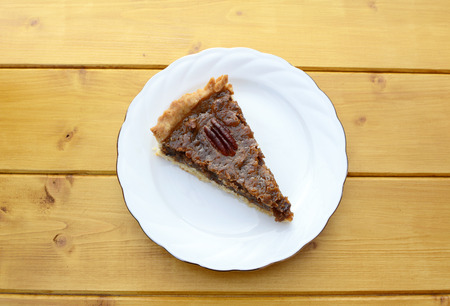 pecan pie: Portion of traditional pecan pie on a white plate on a wooden table