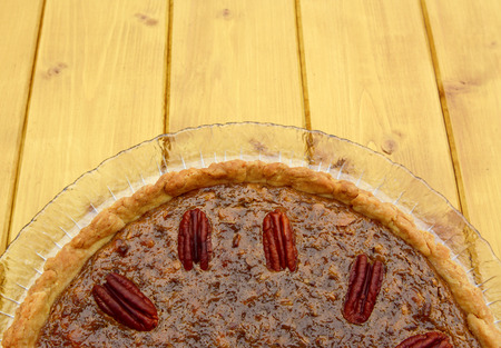 pecan pie: Half view of home-baked pecan pie, with copy space on wooden table
