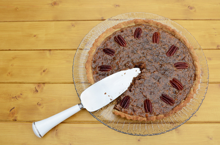 pecan pie: Pie server in a sliced home-made pecan pie on a wooden table