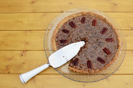 pecan pie: servidor de pastel en un pastel de pacana hecha en casa en rodajas en una mesa de madera