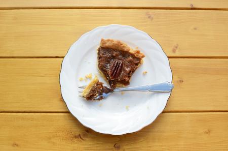 pecan pie: Rebanada de pastel de nuez en un plato de porcelana con un tenedor de postre comido la mitad Foto de archivo