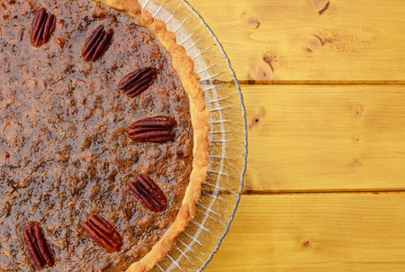 pecan pie: Half pecan pie served on a glass plate, copy space on wooden table Foto de archivo