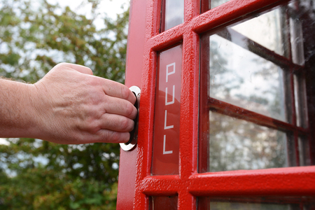 telephone box: Mans hand pulling open red door of an old-fashioned British telephone box Stock Photo