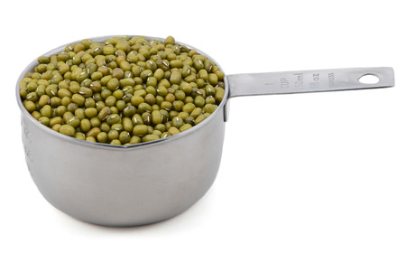 measuring cup: Green mung beans in an American measuring cup, isolated on a white background